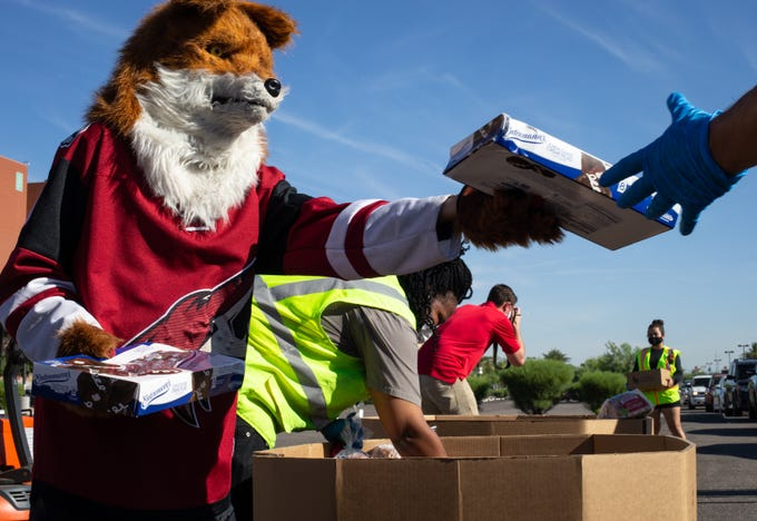 Howler the Coyote helps load St Mary's Food Bank boxes on May 6, 2020, at the Gila River Arena in Glendale.