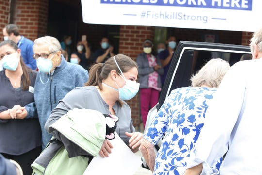 Betty Barclay, 90, enters an SUV to return home to  New Windsor Country Inn with fellow resident Andrew Macenkatrailing behind as they were released from the Fishkill Center for Rehabilitation and Nursing on Wednesday, May 6, 2020. The two recovered from the COVID-19 virus.