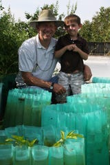 Joey Castle and his grandson, Aidan Miller, grow peppers in Wall-O-Waters in 2012.
