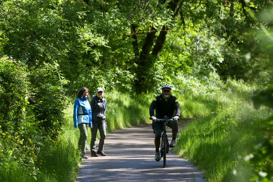 Walkers maintain their social distance from an passing biker at Willamette Mission State Park on Wednesday.
