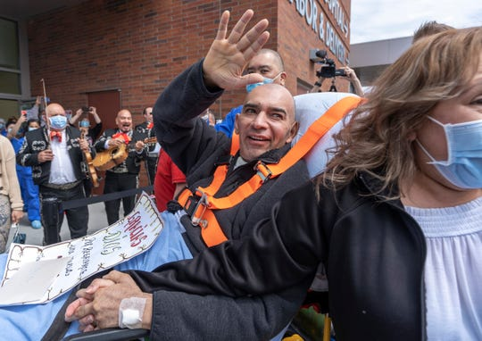 Hector Calderon, joined by his wife, waves to well-wishers as a Mariachi band plays as he's discharged from Kaiser Permanente Westside Medical Center in Hillsboro.