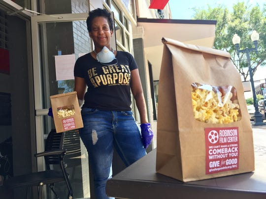 Chef Tootie Morrison of Robinson Film Center's Abby Singer's Bistro takes a break from passing out popcorn to curbside guests during the Give For Good fundraiser on Tuesday, May 5, 2020. Traditional social gatherings were suspended due to the coronavirus pandemic.
