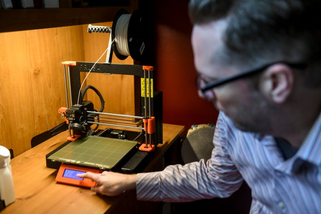 Mitchell Olson resets the 3D printer to make a new batch of testing swabs on Tuesday, May 5, 2020 at his home in Sioux Falls, S.D.