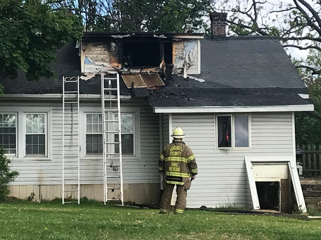 A firefighter surveys the damage to a home Wednesday morning at 175 Mount Pisgah Road.