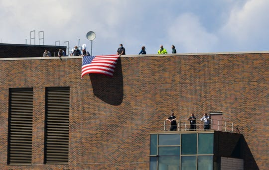 Health care workers fly a flag from the roof of St. Cloud Hospital in anticipation of a flyover by two F-16 Fighting Falcon aircraft from the 148th Fighter Wing of Duluth fly Wednesday, May 6, 2020, in St. Cloud.