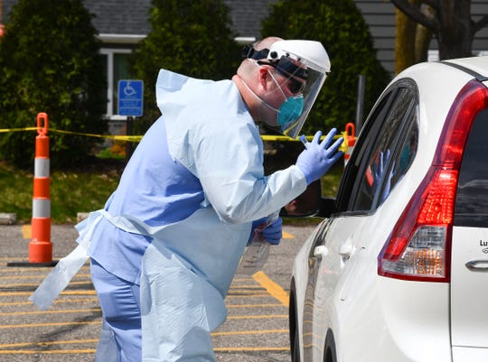 Reed Allanson collects samples from patients in their cars at the curbside collection facility Wednesday, May 6, 2020, at St. Cloud Hospital.