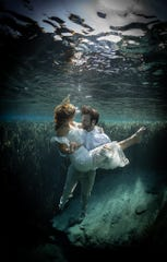 Newlyweds Brian and Kelsey Lovering pose underwater at Jackson Blue Springs after their wedding ceremony at Merritt Mill's Pond in Marianna.