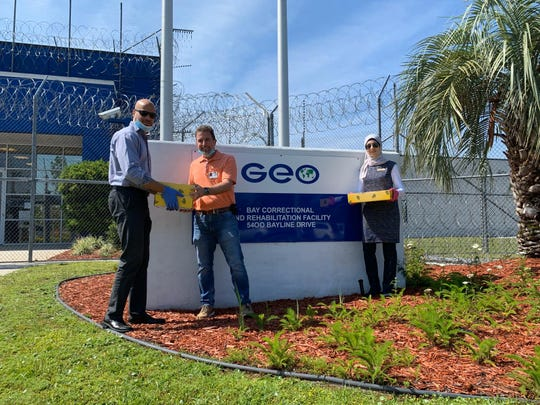 Deyaa Omar with Bay County Islamic Society, left, Jason Jowers, programs manager for Bay Correctional and Rehabilitation Facility, and Hiba Rahim, Muslim Inmates Advocacy Coordinator pose for a photo outside the Bay Correctional Facility as they deliver boxes of dates to Muslim inmates for Ramadan.