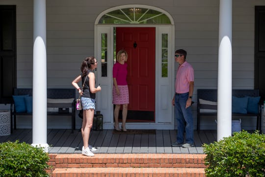 Hettie Spooner, broker and owner of Hill Spooner & Elliott, Inc., talks with a couple on the porch of a home they just finished touring in north Tallahassee Tuesday, May 5, 2020.