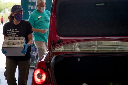Christy Williams, a volunteer from First Presbyterian Church, helps Second Harvest of the Big Bend and Alley Cat Allies to distribute pet food at Legacy Toyota Wednesday, May 6, 2020.