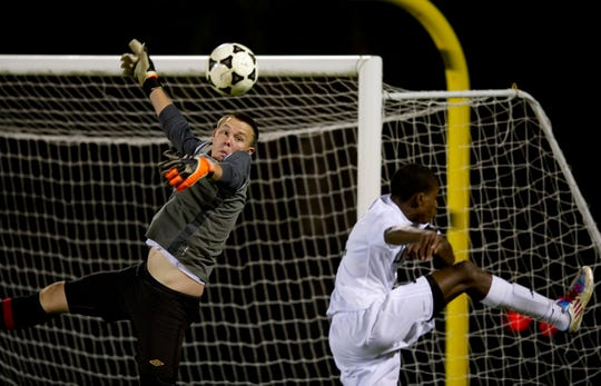 Kyle Gumm, the goalie for St. Lucie West Centennial High School, makes a diving save as Justin Gavin, of Treasure Coast High School, takes a shot on goal during their match at South County Stadium on Jan. 12, 2012.