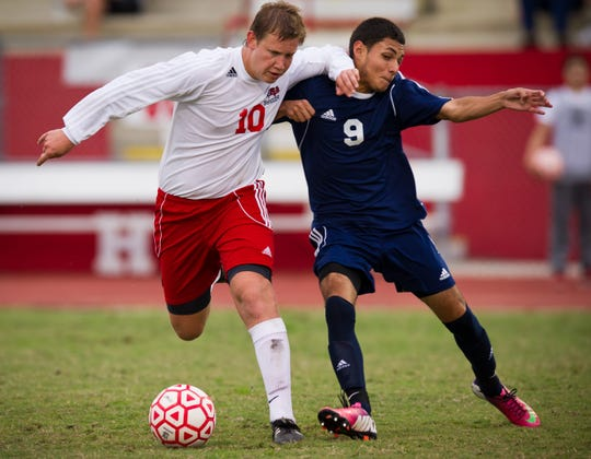 Vero Beach High School's Matt Metz (left) fends off St. Lucie West Centennial High School's Jose Martinez in the second half of play during a first-round boys district soccer game at the Citrus Bowl in Vero Beach on Jan. 20. 2015.