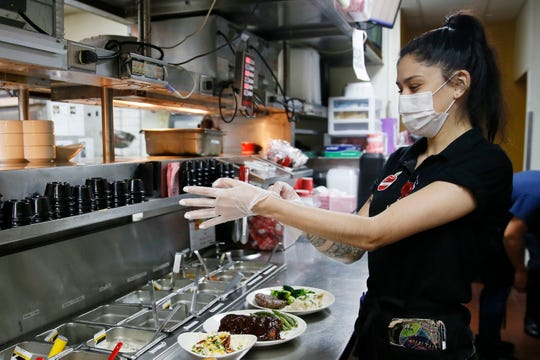 Applebee's server Alexis Gomez puts on a new set of gloves to take food out to the dining room area of the restaurant Wednesday, May 6, at 1766 Airway Blvd. in El Paso.  Applebee's reopened their dining rooms in El Paso on May 1 after being closed six weeks by city and county orders, as part of an effort to curb the spread of COVID-19.