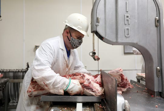 Russ Longwell cuts meat at Phillips Meat Processing near Zanesville recently. Local butchers have seen an uptick in sales since the COVID-19 pandemic started.