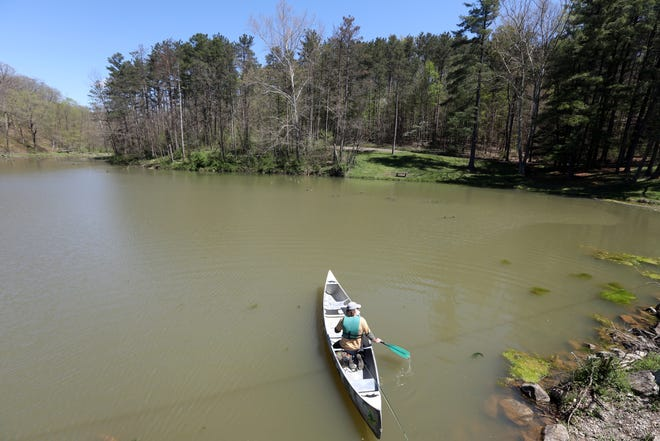 """Al Parker of Canoe Creation paddles at Cutler Lake in Blue Rock State Park. Parker created canoe creation as a way to """"to see people grow in their sense of responsibility, reverence, and respect for the wildlings and wild places of our world and to see people include God in the whole picture."""""""