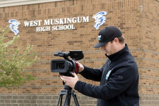 Aaron Spragg of Storied Rivals sets up a camera outside West Muskingum High School. Many schools are going with a virtual graduation, and Storied Rivals is providing video services to a number of local schools.