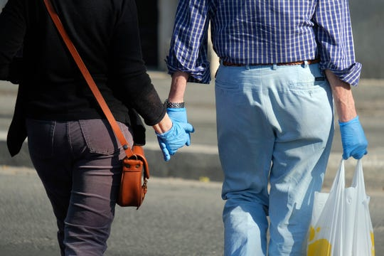 A couple wearing gloves walks hand in hand, in Rome, Wednesday, May 6, 2020. The number of people who have recovered from coronavirus in Italy is higher than the number of people who are actually positive for the first time since Italy created the first red zones on Feb. 21.