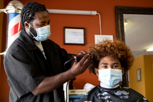 Jurek Williamson, the owner of King's Temple Barber Shop in Memphis, Tenn. cuts the hair of Dashawn Whiting, 16, on May 6, 2020, the first day he is able to reopen his shop during Phase 1 of the city's plan to restart the economy after it was shuttered over fears stemming from spread of the coronavirus pandemic.  (Via OlyDrop)