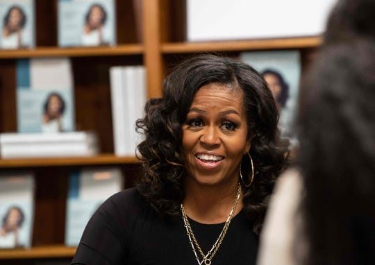 """Former First Lady Michelle Obama meets with fans during a book signing on the first anniversary of the launch of her memoir """"Becoming"""" at the Politics and Prose bookstore in Washington, DC, in 2019. Her bestseller boosted the fortunes of black-owned bookstores."""