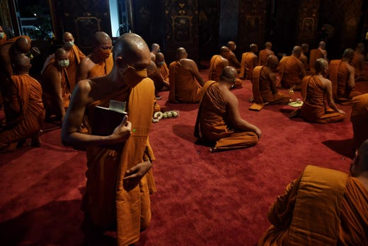 Buddhist monks wearing facemasks take their places for prayers inside the Wat Bowonniwetwiharn temple as Thais are encouraged not to gather inside places of worship, in an attempt to stop the spread of the COVID-19 novel coronavirus, on Visaka Bucha Day in Bangkok on May 6, 2020.
