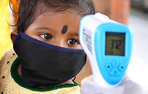 An Indian health worker checks the temperature of a child who had been stranded for weeks due to the lockdown to curb the spread of new coronavirus before allowing her to board a bus, in Bangalore, India, Wednesday, May 6, 2020. India partly relaxed its lockdown this week.