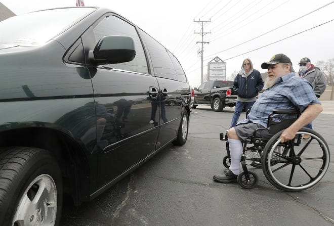 John Pekala, a Vietnam veteran from North Freedom, a village near Baraboo, looks at his new customized van Tuesday in Appleton. Jim Schaefer, also a Vietnam veteran, died from an Agent Orange-related ailment he got in Vietnam, but before he died, Schaefer asked his wife, Susan Ouellette, left, to give the handicap-accessible van to another Vietnam veteran who could use it.