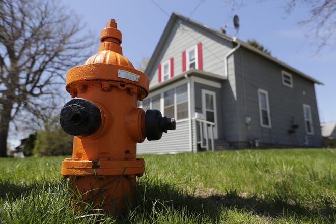 An orange fire hydrant, this one located at the corner of Walter Avenue and Cass Street in Appleton, has a water flow rate between 500 and 999 gallons per minute.