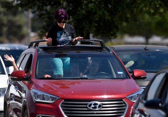 Denise Davidson prays through the sunroof of Christine Wilson's car during Thursday's National Day of Prayer service.