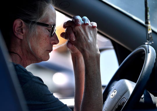 Kim Heye prays from behind the wheel of her car during Thursday's National Day of Prayer service.