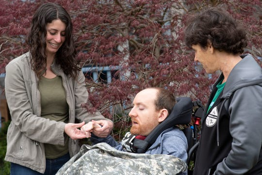 Melissa Vigil, RN, holds the hand of her patient, Danny Oleksa, with his mom, Laurie Oleksa, on Tuesday, May 5, 2020 at his home in Battle Creek. Home health care is a lifeline for nearly 12 million Americans, the majority of them among someof the most vulnerable populations to the coronavirus.