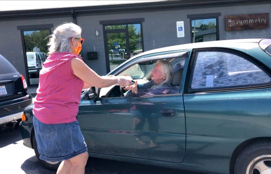 A Food Connection volunteer hands food to a Swannanoa Valley resident.