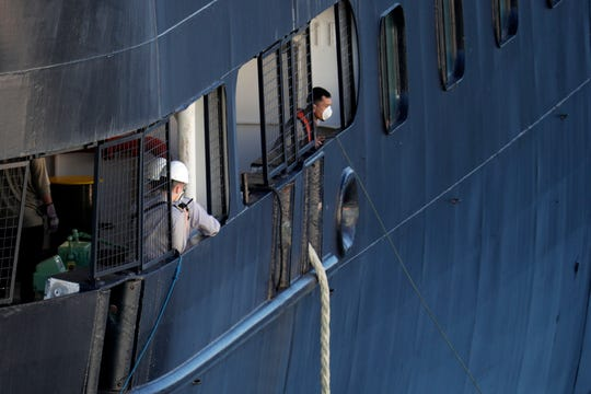 Crew members look out from the Carnival's Holland America cruise ship Zaandam as it docks at Port Everglades during the new coronavirus pandemic, Thursday, April 2, 2020, in Fort Lauderdale, Fla. Several passengers have died from COVID-19 after trips on the ship, according to state Medical Examiner data. (AP Photo/Lynne Sladky)