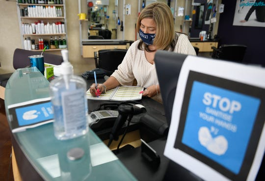 Angela Ortiz writes down clients in the schedule as Super Cuts prepares to reopen, Thursday, May 7, 2020. Hair salons, barbershops and nail salons can reopen as part of Gov. Greg Abbott's plan to reopen.