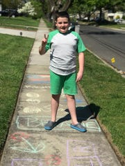 Tavit Murray of Cherry Hill enjoys his family's sidewalk obstacle course that inspires passersby to jump, pin, leap, wiggle and breathe.