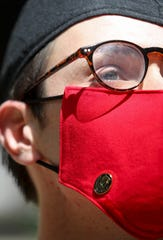 Oliver Smith, wearing his face mask and pin, stands in the sunlight after attending his drive-thru pinning ceremony at APSU's McCord building in Clarksville, Tenn., on Thursday, May 7, 2020.