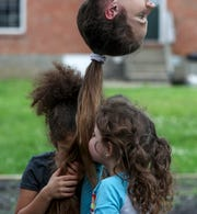 While Brittany King hangs from the monkey bars, Kaylee, left, 8, and Emma, right, 6, smell and play with their mother's hair at the neighborhood park at the King home in Clarksville, Tenn., on Tuesday, May 5, 2020.