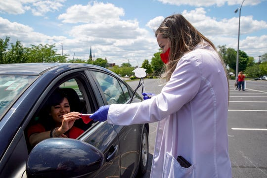 Dr. Bettina Shank, assistant director, hands out pins attached to face masks during their drive-thru ceremony at APSU's McCord building in Clarksville, Tenn., on Thursday, May 7, 2020.