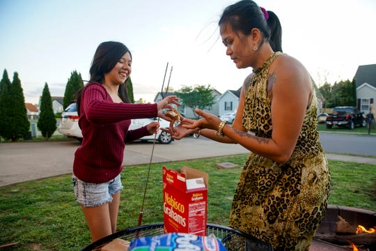 Ailene Jordan, right, helps her daughter Liliane, 12, left, construct a s'more at the Jordan household in Clarksville, Tenn., on Thursday, April 30, 2020.