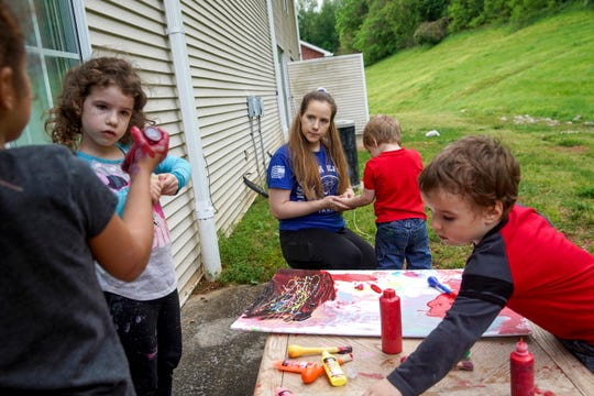 The King children share paint and poster boards while Brittany King, center, examines her son Cooper's hands at the King home in Clarksville, Tenn., on Tuesday, May 5, 2020.