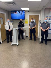 From left, Linden Police Chief David Hart, Capt. Joe Cacioppo, Lt. Andy Bara and Capt. Don Geisheimer stand with a portable UV-C generator purchased with funds provided by Phillips 66 Bayway Refinery.
