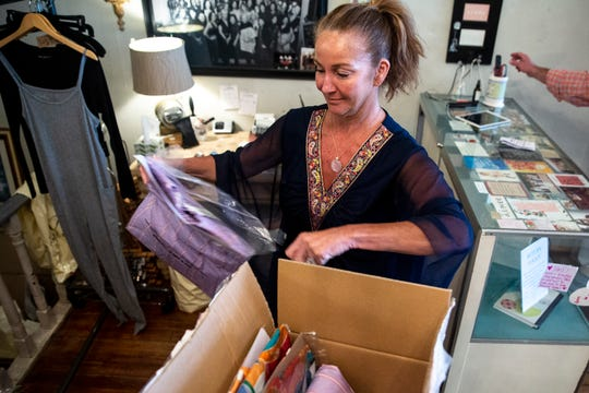 Amy Hassebrock, owner of the boutique clothing store Aimee in Des Moines' East Village, opens a new shipment of clothing from Paris, on Thursday, May 7, 2020, in preparation to reopen her shop tomorrow as state restrictions on retail stores, put in place because of COVID-19, are set to be lifted.