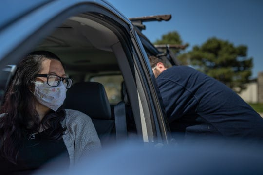 Brittany Jennings sits in her vehicle while waiting to pick up food items from the MCREST building in Roseville on May 6, 2020 with her fiancé Chris Banuelos.
