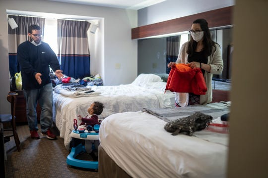 Chris Banuelos reaches for his son as he and his fiancée, Brittany Jennings, prepare to leave their hotel room in Roseville to go to MCREST to pick up food on May 6, 2020.