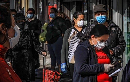 Women in Brooklyn's Sunset Park, a neighborhood with one of the city's largest Mexican and Hispanic community, wear masks to help stop the spread of coronavirus while waiting in line to enter a store, Tuesday May 5, 2020, in New York. A poll found that 61% of Hispanic Americans say they've experienced some kind of household income loss as a result of the COVID-19 outbreak.
