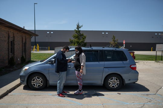 Chris Banuelos and his fiancée Brittany Jennings wait in the parking lot to pick up food and supplies from MCREST in Roseville on May 6, 2020.
