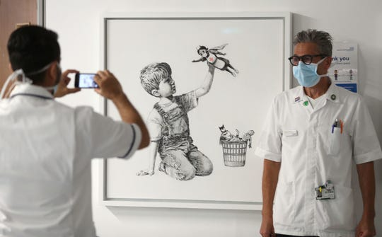 A member of staff has their photograph taken in front of the new artwork painted by Banksy during lockdown, entitled 'Game Changer', which has gone on display to staff and patients on Level C of Southampton General Hospital in Southampton, England, Thursday.