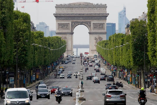 Cars drive on the Champs Elysee avenue, Thursday, May 7, 2020 in Paris. The French. government will announce later Thursday measures for the post-lockdown which is expected Monday.