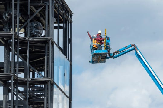 Workers continue building a Carvana car dealership under construction in Novi on Thursday, May 7, 2020.  Carvana is an online used car retailer that sells vehicles using multi-story car vending machines.