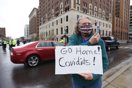 Karen Spitler of Lansing , an counter-protesters holds a sign during a rally at the state Capitol in Lansing, Mich., Thursday, April 30, 2020.