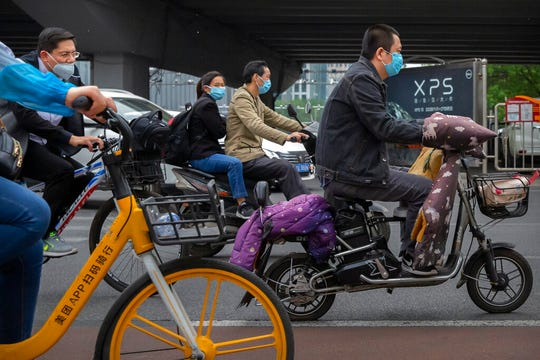 People pass by wearing face masks to protect against the spread of the new coronavirus as ride along a street in Beijing, Wednesday, May 6, 2020. China on Wednesday reported just two new cases of the coronavirus and no deaths.